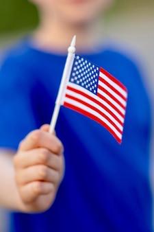 Recortada de la mano que sostiene la bandera americana.