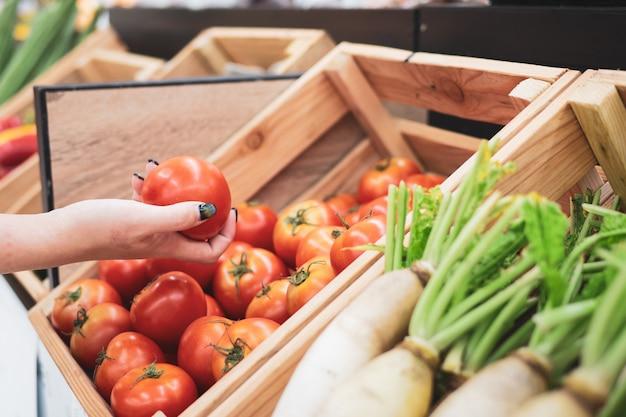 Recortada de mujer joven comprando frutas en el mercado del agricultor