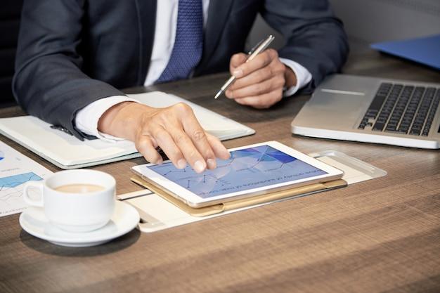 Recortar empresario usando tableta en mesa