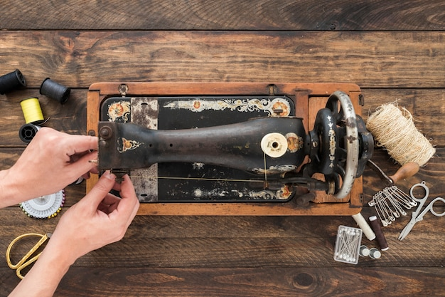 Recortar las manos ajustando el hilo en la vieja máquina de coser