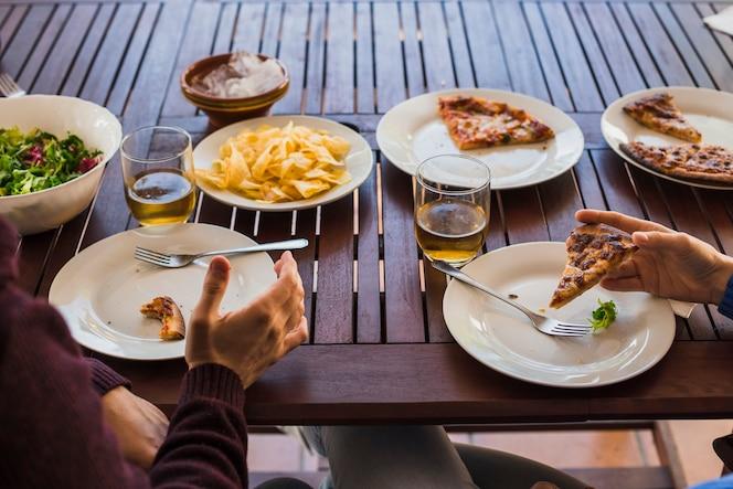 Recortar las manos del hombre y la mujer almorzando