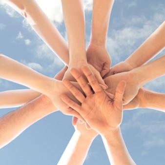 Recortar las manos en círculo en el cielo azul