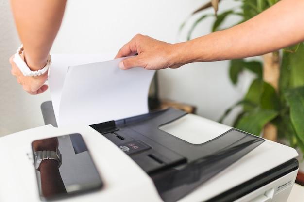 Recortar las manos tocando el papel en la impresora