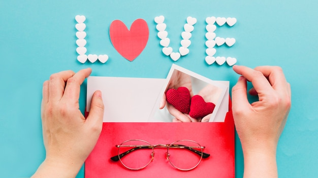 Recortar las manos abriendo el sobre cerca de escribir el amor