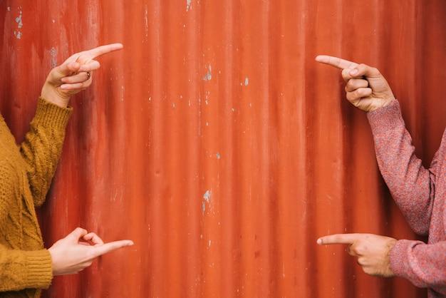 Recortar las manos apuntando a la pared de metal naranja