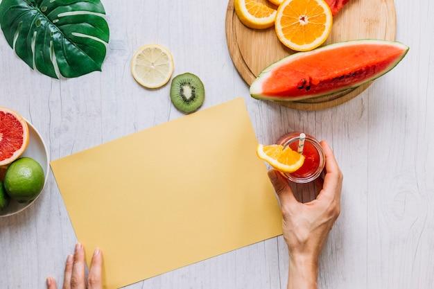 Recortar las manos con un batido cerca de papel naranja y frutas