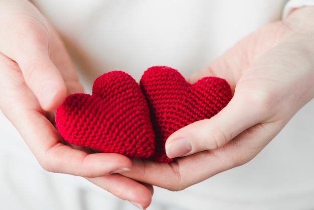 Recortar las manos con corazones tejidos
