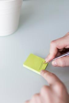 Recortar las manos dibujando líneas en una nota adhesiva