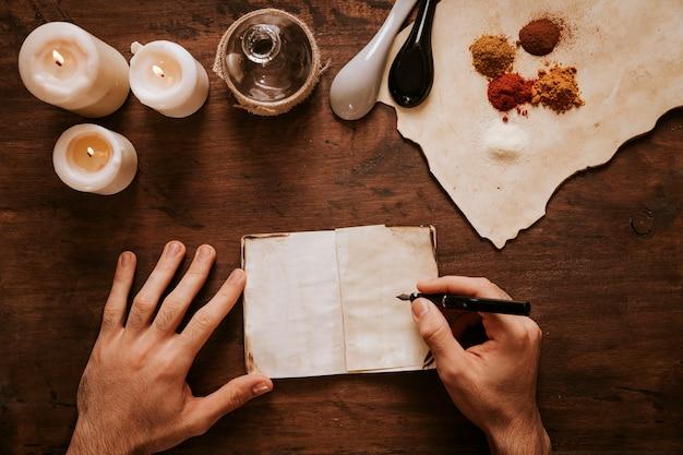Recortar manos escribiendo cerca de velas e ingredientes