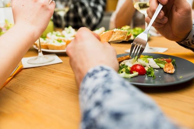 Recortar las manos del hombre comiendo delicioso plato