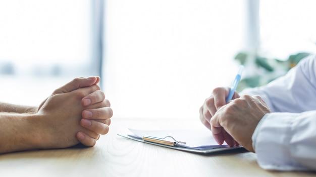 Recortar las manos del médico y el paciente en el escritorio