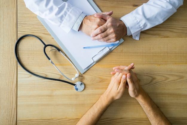 Recortar las manos del paciente masculino y médico en la mesa