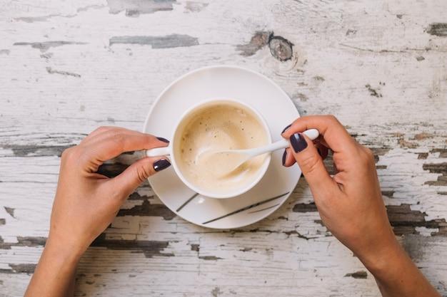 Recortar las manos revolviendo el café
