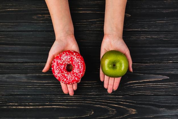 Recortar las manos sosteniendo donas y manzana