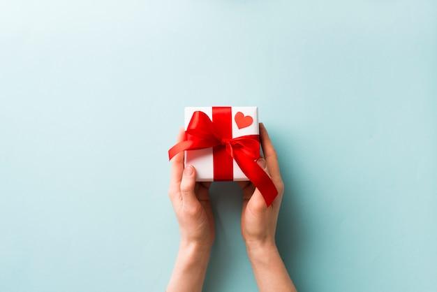 Recortar las manos sosteniendo una pequeña caja de regalo