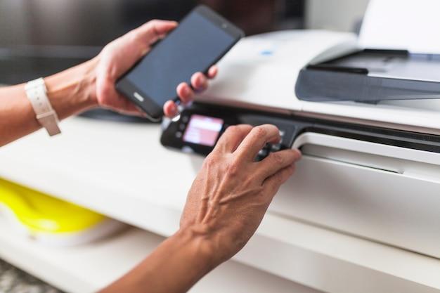 Recortar las manos con el teléfono inteligente con la impresora