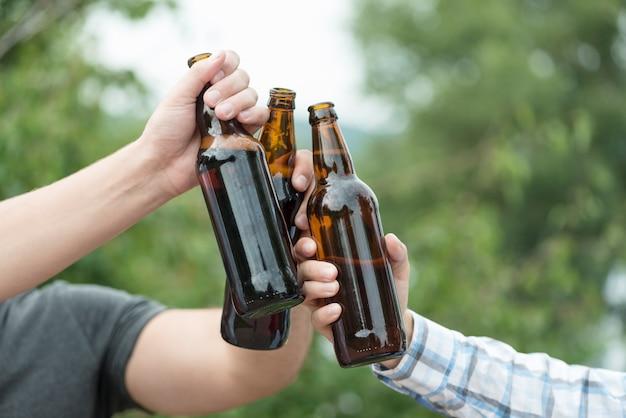 Recortar las manos tintineantes botellas de cerveza en la naturaleza