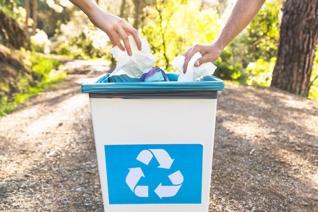 Recortar las manos tirando basura en la papelera en el bosque