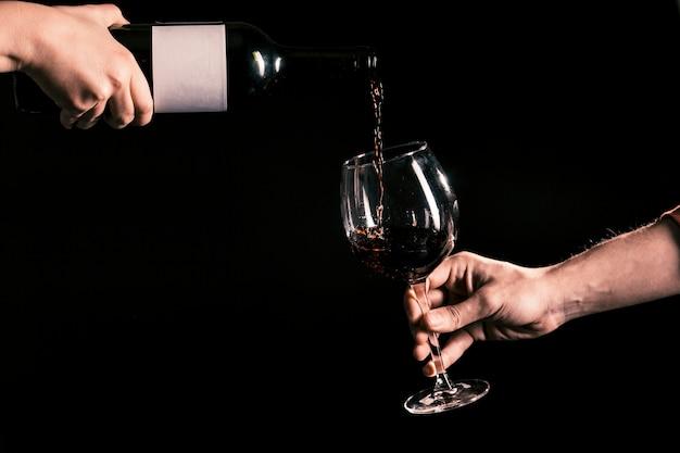 Recortar las manos vertiendo vino en vidrio