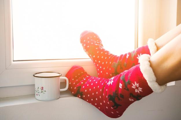 Recortar las piernas y la taza cerca de la ventana