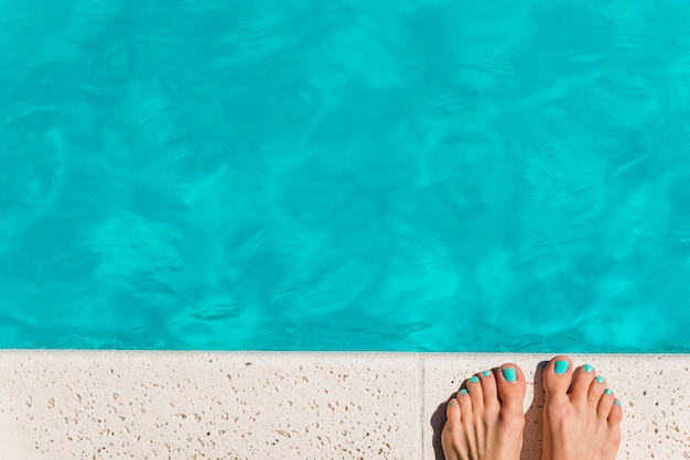 Recortar pies femeninos junto a la piscina