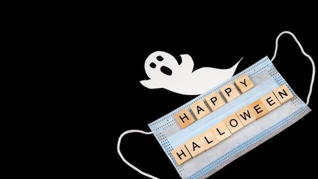 Recorte el fantasma de papel, la máscara médica y las palabras feliz halloween en negro