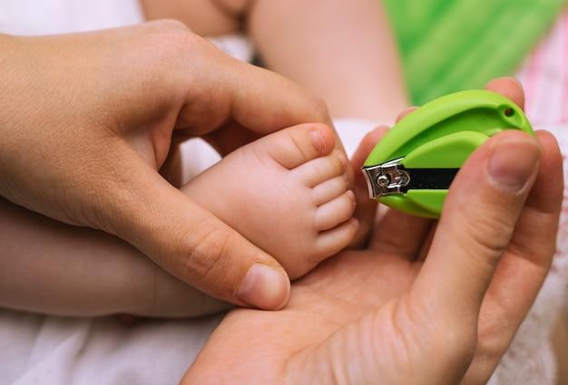Recorte de uñas para un niño pequeño. pedicure. pequeños pies y manos de mamá. higiene.