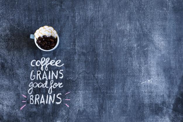 Recorte de papel del cerebro y granos de café en taza con texto en la pizarra