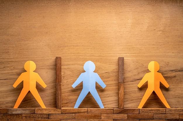 Recorte de papel figuras humanas separadas por bloques de madera en la pared de madera