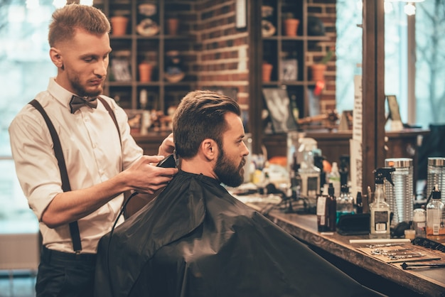 Recorte perfecto en peluquería. joven barbudo cortarse el pelo por peluquero con maquinilla de afeitar eléctrica
