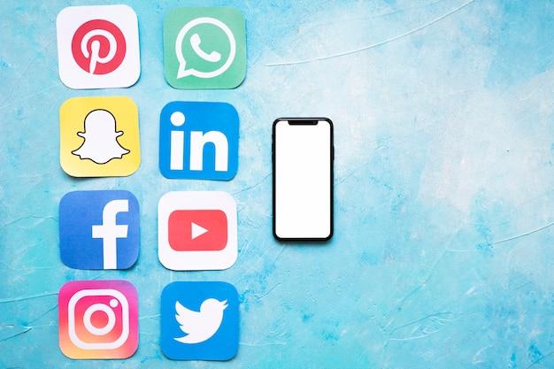 Recortes de papel de iconos de redes sociales dispuestos cerca de teléfono inteligente