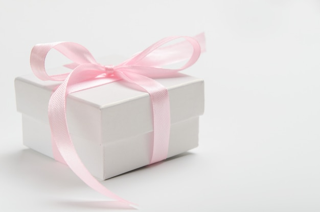Rectángulo de regalo blanco en un blanco con una cinta rosada.