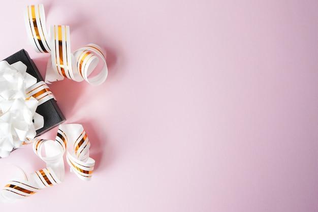 Rectángulo de regalo en cinta del oro en fondo rosado. copia espacio