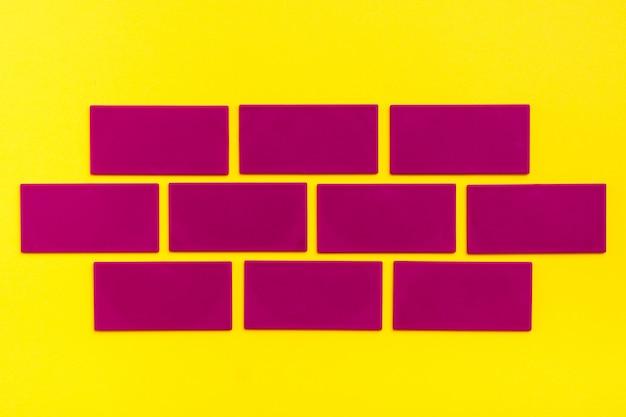 Los rectángulos planos púrpuras imitan el ladrillo sobre cartón amarillo. vista superior. concepto de creación