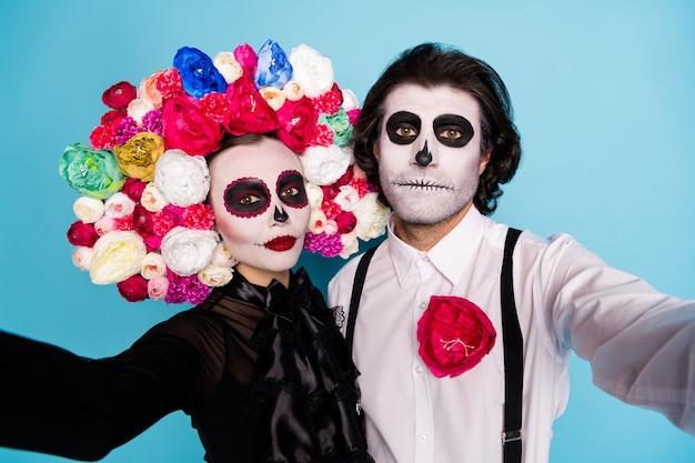 Recuerdos festivos. foto de primer plano de la bonita pareja de zombies hombre dama abrazo tomar selfie mirada romántica usar vestido negro traje de muerte rosas diadema tirantes fondo de color azul aislado