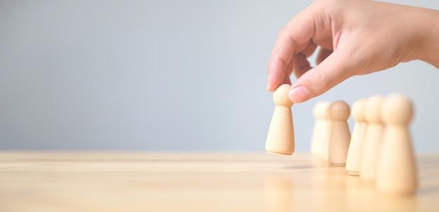 Recursos humanos, gestión del talento, reclutamiento de empleados, concepto exitoso de líder de equipo de negocios. mano elige a un pueblo de madera que se destaca de la multitud