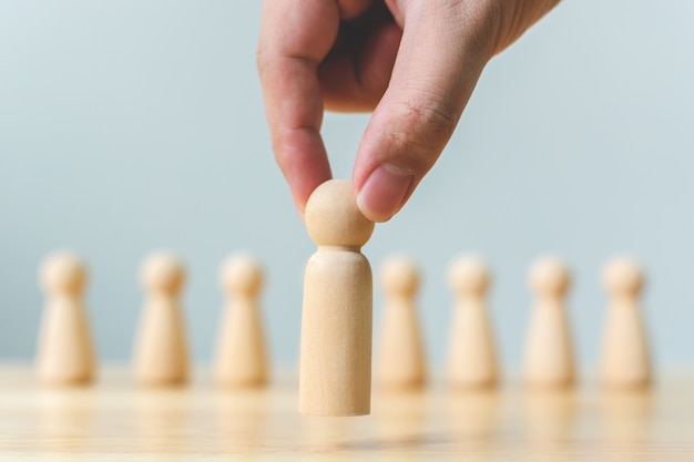 Recursos humanos, gestión del talento, reclutamiento de empleados, concepto exitoso de líder de equipo de negocios. mano elige a un pueblo de madera que se destaca entre la multitud.
