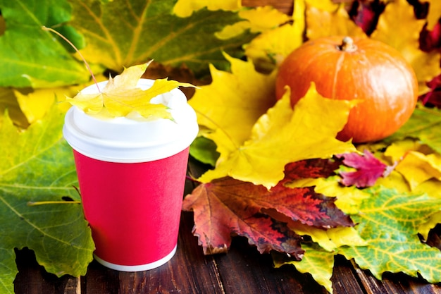 Red coffee to go cup witn marple leaf and pumpkin