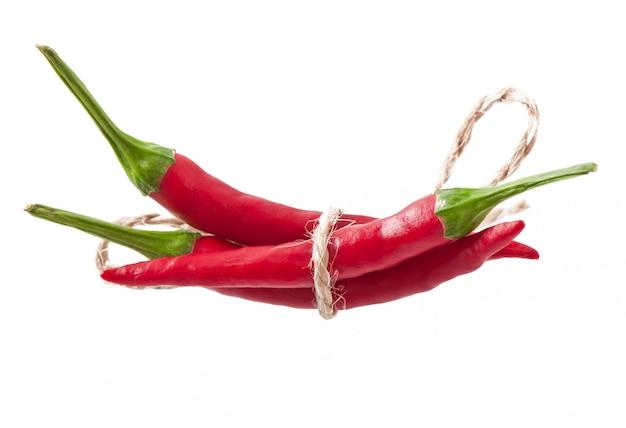 Red hot chili peppers atados con una cuerda en blanco