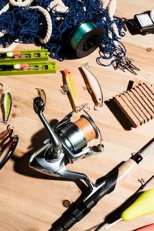 Red de pesca; carrete de pesca; señuelos y caña de pescar sobre fondo de madera