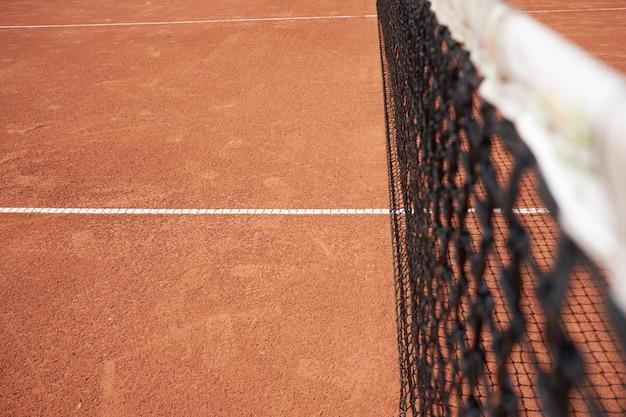 Red de tenis en campo de arena roja