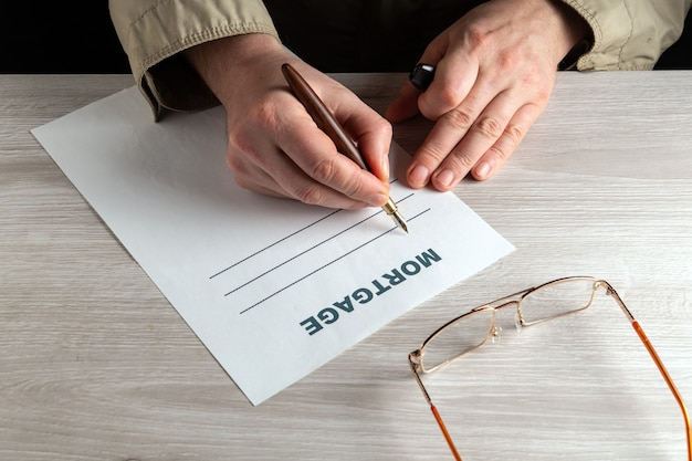 Redacción de hipoteca en un entorno de trabajo sobre el escritorio. primer plano de las manos del hombre llenando el espacio en blanco con lápiz