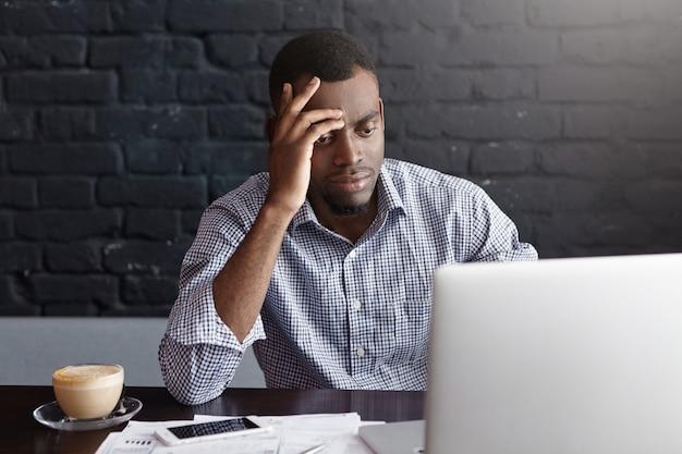Redactor afroamericano concentrado con exceso de trabajo vistiendo camisa