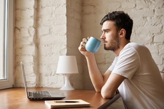 Redactor guapo con barba elegante sosteniendo una taza con café en la mano
