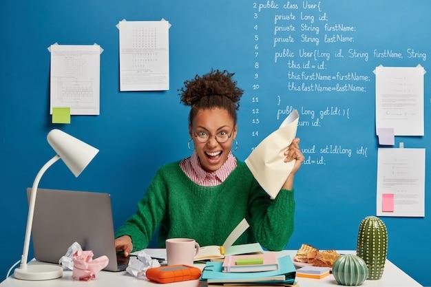 Redactora emocional femenina de piel oscura arruga papeles en la mano, trabaja en una computadora portátil moderna, escribe información en el bloc de notas