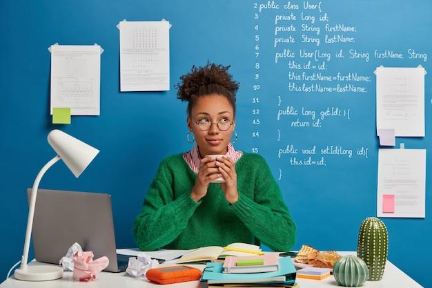 Redactora exitosa trabaja en un proyecto en línea, mira pensativamente a un lado, bebe café aromático, posa en una acogedora sala de estudio