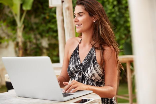 La redactora femenina hermosa complacida busca información en diferentes páginas web en internet, hace trabajo diferente en la computadora portátil, hace la presentación.