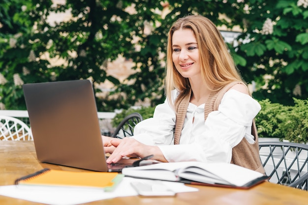 Redactora rubia concentrada trabajando en tareas creativas