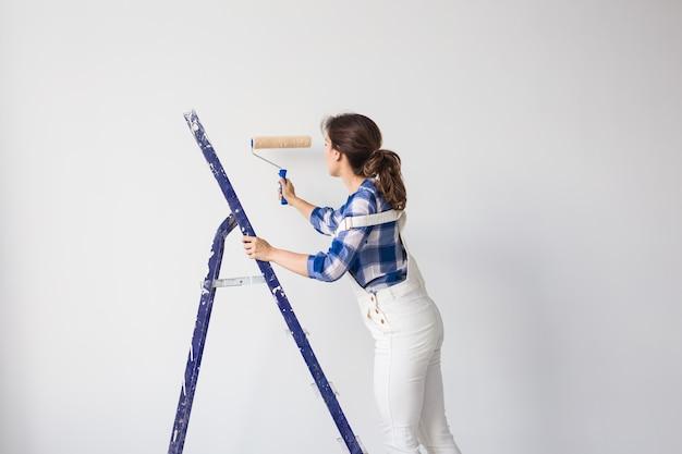 Redecoración, renovación, nuevo hogar y concepto de personas - pintora haciendo reparaciones por sí misma