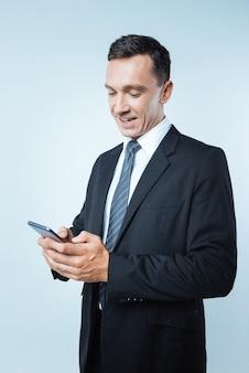 Redes sociales. encantado de hombre de negocios alegre positivo sosteniendo su teléfono inteligente y escribiendo un mensaje mientras habla en línea